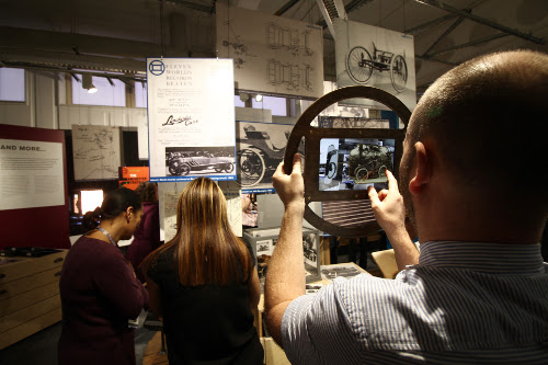An augmented reality tablet in a car steering wheel shaped frame being used in the Lanchester Interactive Archive space at Coventry University library, 2017.