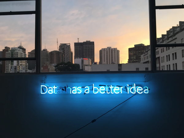 View from a window across the city. In the foreground a neon light says 'Data has a better idea'.