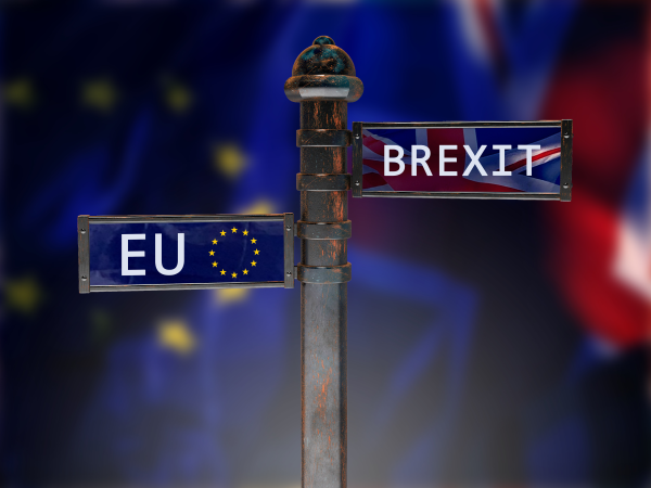 Finger signpost with arms pointing to EU and Brexit, against background of UK & EU flags